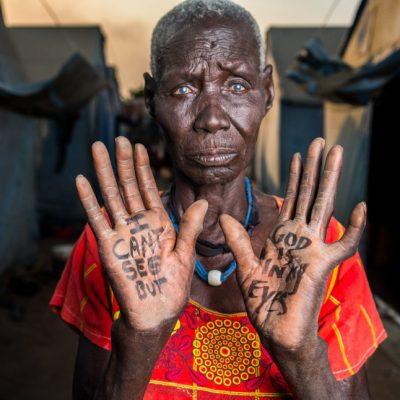 """""""Non posso vedere, ma Dio è nei miei occhi"""". Caroline Ako, Mangaten Camp, è cieca e si sente spersa nel campo profughi. Ma ha voluto comunicare la sua profonda fede in Dio."""